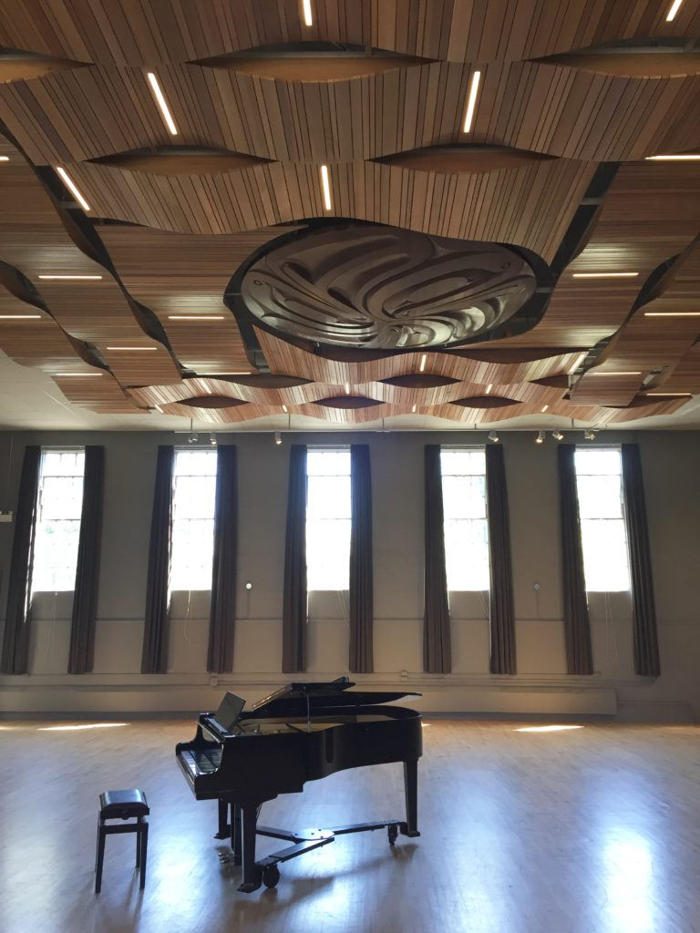A grand piano sits open a ready to be played, in fron of a back drop of 20 foot high windows that spill light on to a hardwood floor. Above hangs a cedar acoustic ceiling.